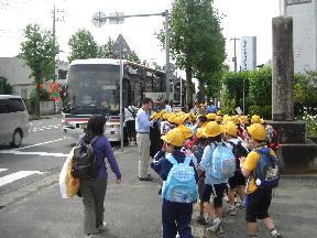 小学校前からバスに乗車する子どもたち