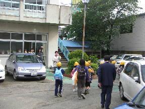 保健室前で,職員に見送られ出発する子どもたち