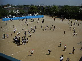 昼休みグラウンドで遊ぶ子どもたち グラウンド東側には,臨時の駐車場ができました。\