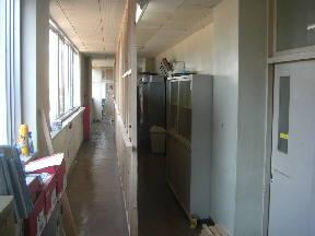 職員室前から保健室に通じる廊下が,板で仕切られました。左側の部分は,来年3月までに新築の特別支援教室棟と結ばれる予定です\