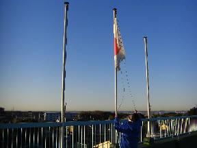快晴の下,国旗を掲揚する加藤教諭