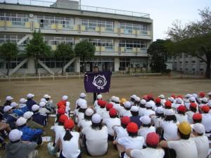 校旗を手に説明する体育主任