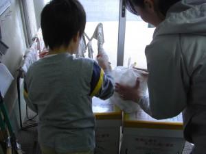 「たくさん持ってきたよ!」担任の先生と回収箱に入れる2年生\