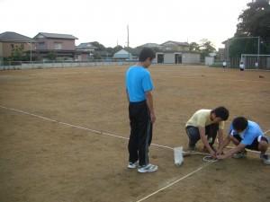 グラウンドにロープを敷設する本校職員(17:40)