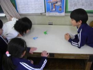 折り鶴に息を吹きかけ紙すもうで遊ぶ子供たち(10:25)