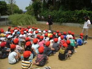 たねのまきかたについて学年主任の先生の話を聞く子どもたち(10:40)