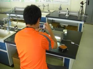 顕微鏡で,いろいろな葉を用いて気孔の見え方をチェックする本校職員(17:50)