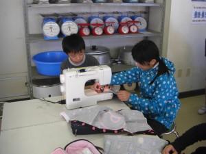 協力し合いながら,ミシンでエプロンを縫っています(11:10)
