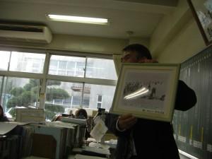 大正14年下津海岸で行われた,本校水泳学習の写真を手にお話をする校長先生(8:25)