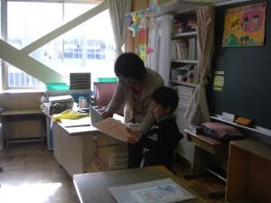 担任の先生から通知表をもらう1年生(10:10)