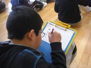 イラストと手本を参考にアルファベットを書いています。(9:30)