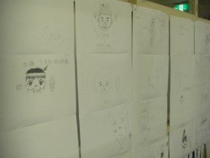 教室に飾られた子どもたちの作品です。先生の大好物なども上手に描かれていますね。(16:35)