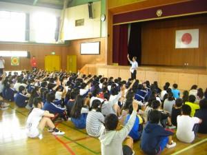 校長先生の問いかけに挙手をする子どもたち(8:10)