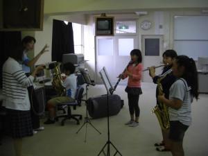 顧問の先生の指揮に合わせて演奏収録を行う吹奏楽部の6年生(13:20)