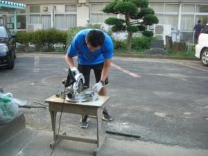 電動のこぎりで,実験用具の作成を進める本校職員(17:30)
