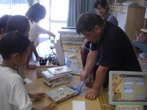 バーコードリーダーを操作して,図書の貸し出しを行う教頭先生(13:05)