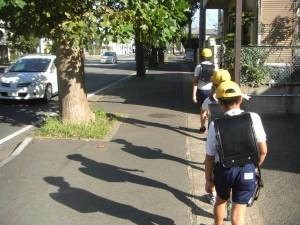 一列に並んで学校へ向かう子どもたち 子どもたちの影も 季節のうつりかわりとともに,少しずつ長くなりつつありますね。(7:50)