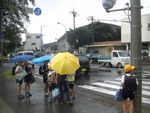 にわか雨が降り始め,傘をさし信号を待つ子どもたち(7:40)