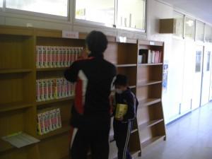 国語辞典,漢字辞典を新しい書架に置く図書委員と担当職員(15:20)