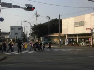 やわらかな朝の日差しを浴びながら,鹿島小前交差点を横断する子どもたち(7:55)