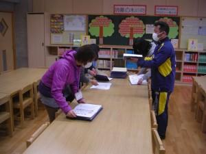 卒業証書の確認をする本校職員(17:00)