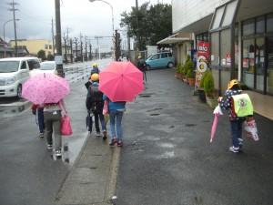 小雨の中,学校へと向かう子どもたち(7:30)