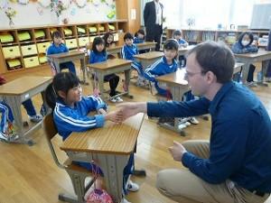 1年生が「ジェラルド先生と遊ぼう」を計画しました。最初は自己紹介で全員が握手をしました。\