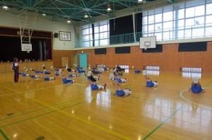 陸上の練習が外で出来ないので,今日は体育館です。準備体操をしています。\