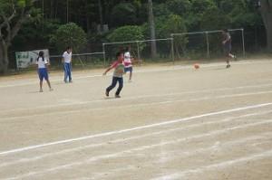 教務主任の榎本先生,⒍年生とサッカーをしています。今,蹴ったところです。\
