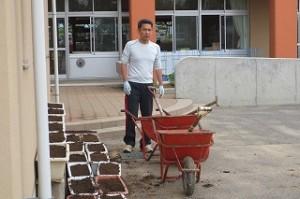プランターの土を一輪車にいれ,肥料足して混ぜ合わせ,またプランターに入れました。\