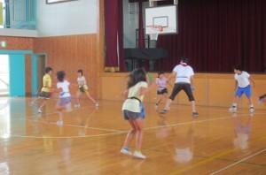 4・5年生が体育館で「シッポトリ」のゲームをしています。ステージ前にいる背の高い後藤先生も一生懸命です。\