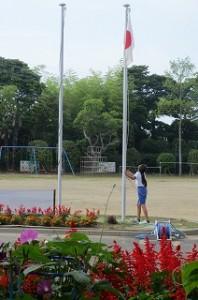 ⒍年生の日直が国旗を掲揚しています。\