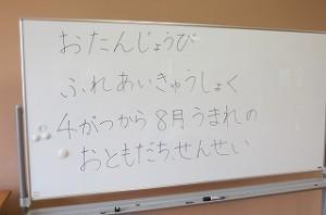 ホワイトボードに「お誕生日 ふれあい給食 4~8月の生まれのお友達と先生」と書かれています。\