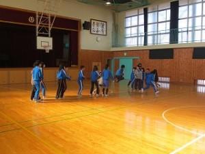体育館の一番奥ステージ前で練習をしています。全校児童が3つに分かれています。\