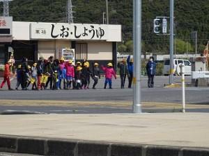 この写真は,道路の歩き方や横断歩道の渡り方を実際に体験して学ぶ豊津小学校の交通安全教室です。信号のある横断歩道を渡っています。\