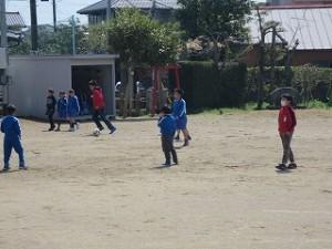 6年生と下学年の子が一緒にサッカーをして遊んでいます。\