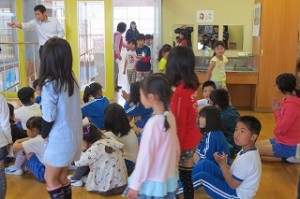 1年生が2年生に手をつながれて入場してきました。手拍子をして迎えます。\