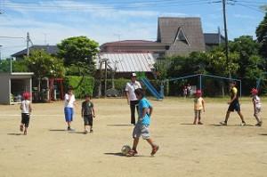 今日はとってもよい天気。昼休み,6年生担任の後藤先生と子どもたちでサッカーをして遊んでいます。\