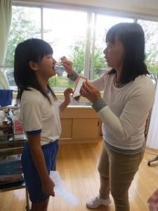磨き残したところをきれいにするために歯ブラシの当て方,動かし方を保健の先生に教わっています。\