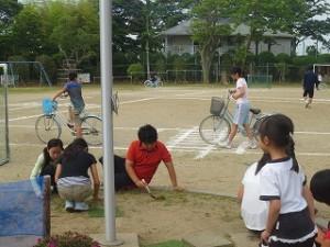 ⒍年生,朝の奉仕活動です。向こうでは自転車大会の「安全走行」の練習をしています。\