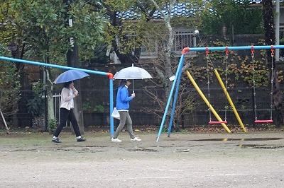 雨の中,遊具の安全を点検しています。\