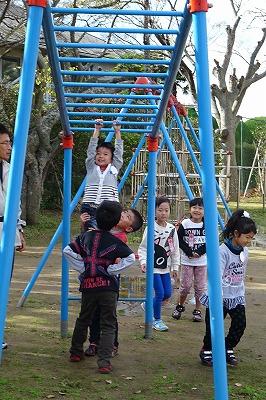 幼稚園の男の子が雲梯に挑戦! 1つ進みました。高いので1年生が支えています。\